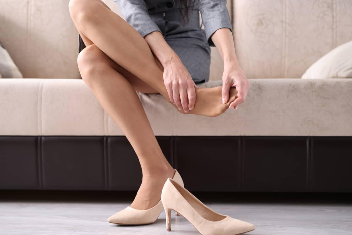 Kobieta masuje bolącą stopę. Problemy stóp.