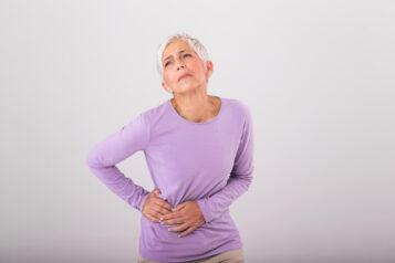Kobieta trzyma się zabiodro. Jakie mogą być przyczyny bólu biodra?