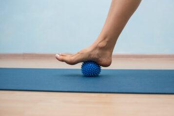 Kobieta masuje podeszwę stopy. Skuteczna rehabilitacja przy leczeniu ostrogi piętowej.