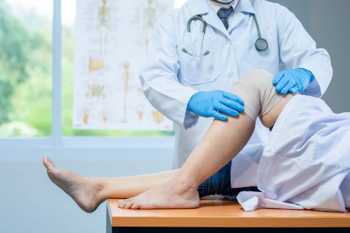 Lekarz bada kolano pacjenta. Uszkodzenie więzadła krzyżowego przedniego