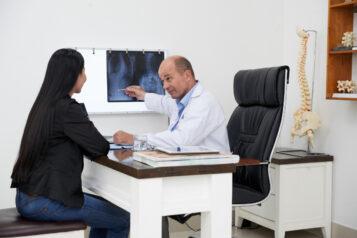 Lekarz objaśnia pacjentce zdjęcie rtg kręgosłupa. Choroba Scheuermanna - czym jest ijak się objawia