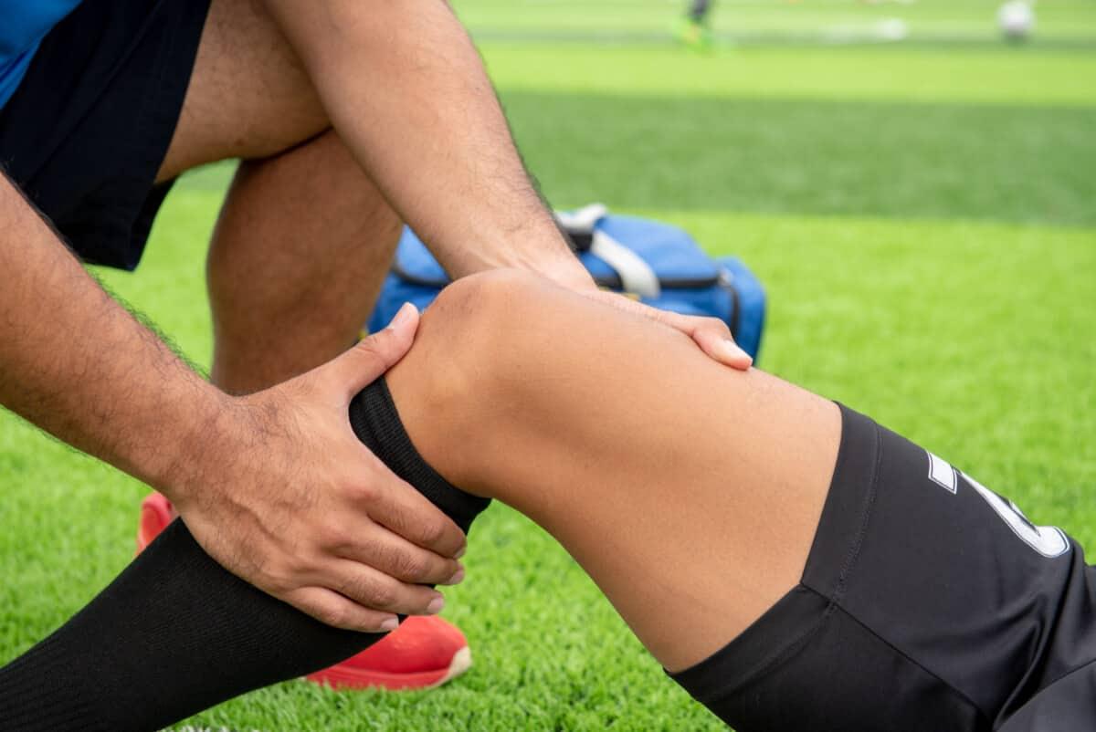 Lekarz sprawdza kolano piłkarza. Najczęstsze urazy piłkarzy zawodowych i amatorów