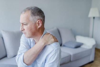 Mężczyzna trzyma się za bolący bark. Urazowe uszkodzenia ścięgien pierścienia rotatorów stawu barkowego