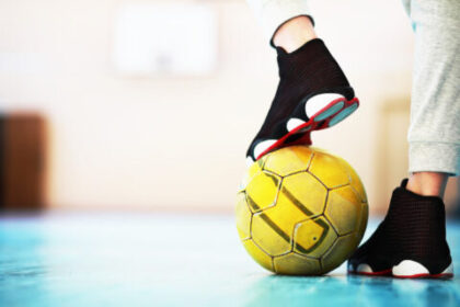 Mężczyzna z piłką pod butem. Urazy w piłce nożnej halowej - jak możesz ich uniknąć