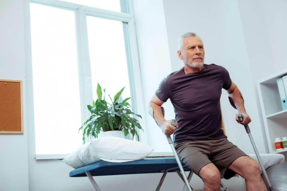 Mężczyzna wstaje z łóżka o kulach. Dwa dni po endoprotezie biodra - czy można już normalnie funkcjonować?