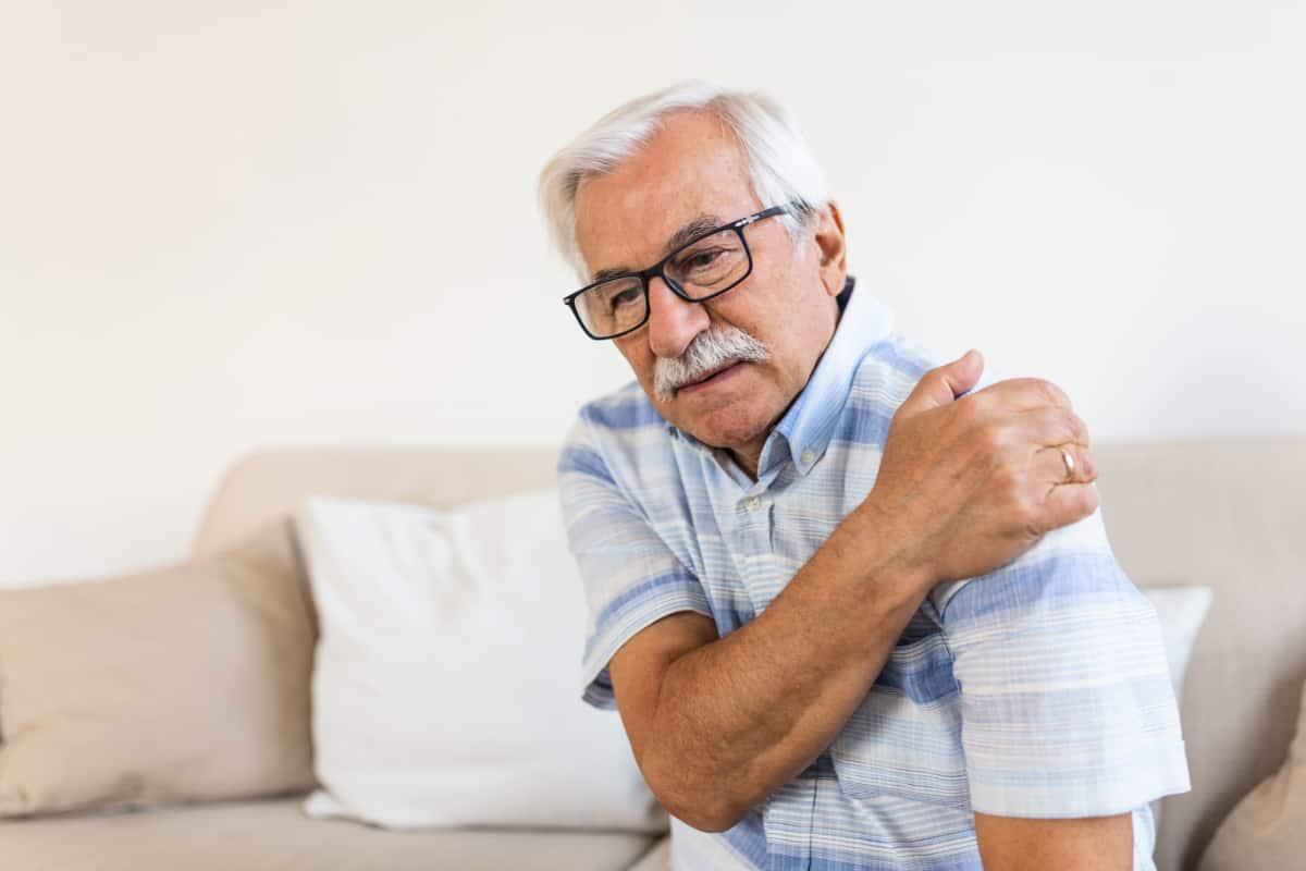 Starszy mężczyzna trzyma się za bolący bark. Protezoplastyka stawu barkowego - od czego zależy rodzaj stosowanej protezy