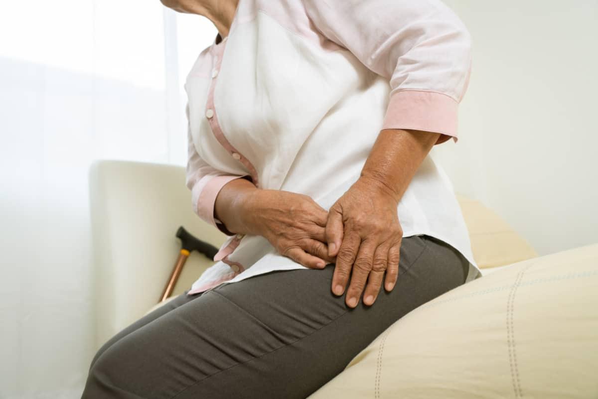 Kobieta trzyma się za bolące biodro.