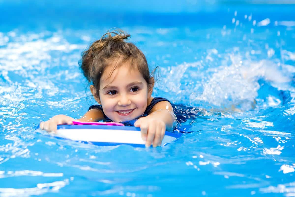 Mała dziewczynka uczy się pływać. Dlaczego warto pływać ichodzić nabasen