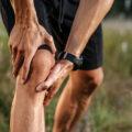 Mężczyzna trzyma się zabolące kolano. Niestabilność rzepki - jakie są objawy imetody leczenia