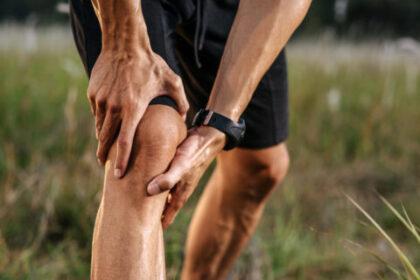 Mężczyzna trzyma się za bolące kolano. Niestabilność rzepki - jakie są objawy i metody leczenia