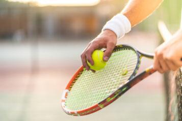 Tenisista zrakietą ipiłką przy siatce. Sporty jednostronne - uważaj nakontuzje